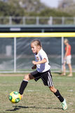 女孩青年足球踢球的足球运动员 免版税库存图片