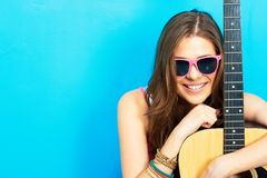 女孩音乐家坐与吉他的一个地板 免版税图库摄影