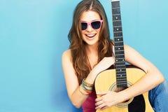 女孩音乐家坐与吉他的一个地板 库存图片