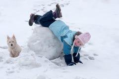 女孩顶头脚跟位于在随风飘飞的雪 免版税库存照片