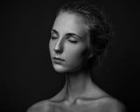 女孩题材的剧烈的画象:一个美丽的女孩的画象黑暗的背景的在演播室 免版税库存图片