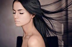 女孩题材的剧烈的画象:一个美丽的孤独的女孩的画象有飞行头发的在黑暗的背景隔绝的风  免版税库存照片