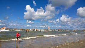 女孩风帆冲浪者去海 免版税库存照片
