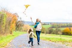 女孩飞行秋天的一只风筝或跌倒草甸 免版税图库摄影