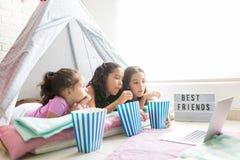 女孩食用玉米花,当观看在膝上型计算机的电影在帐篷时 库存图片