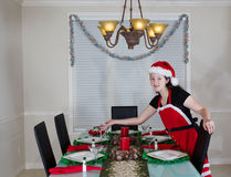 女孩餐桌为圣诞晚餐做准备 免版税库存图片