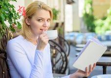 女孩饮料咖啡,当由普遍的作者时的读的畅销书书 抢劫完善咖啡和有趣的书最佳的组合 库存照片