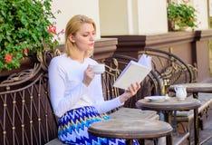 女孩饮料咖啡,当由普遍的作者时的读的畅销书书 读书是她的爱好 杯子咖啡和有趣的书 免版税库存图片
