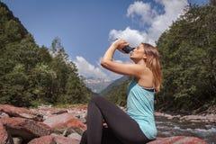 女孩饮用水和坐石头在河 免版税库存图片