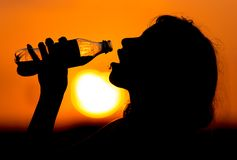 女孩饮用水的剪影在日落的 免版税库存图片