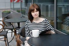 女孩饮用的咖啡和使用片剂计算机 图库摄影