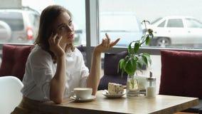女孩饮用的咖啡和谈话在咖啡馆的手机 关于在午休的业务材料的女商人讨论 库存图片