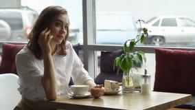 女孩饮用的咖啡和谈话在咖啡馆的手机 午休的女商人 库存图片
