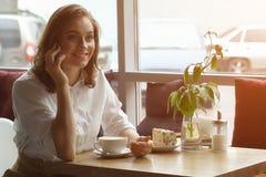 女孩饮用的咖啡和谈话在咖啡馆的手机 午休的女商人 图库摄影