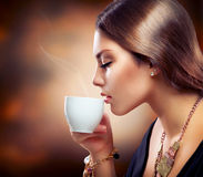 女孩饮用的咖啡或茶 免版税库存照片
