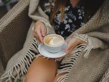 女孩饮用的咖啡的特写镜头 在杯子的美丽的拿铁 妇女藏品为在被弄脏的咖啡馆背景的咖啡服务 库存照片