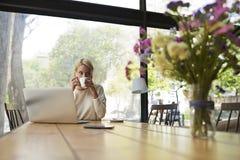 女孩饮用的茶在您的膝上型计算机的设计师餐馆和检查邮件 免版税库存图片