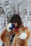 女孩饮用的茶在森林 库存照片