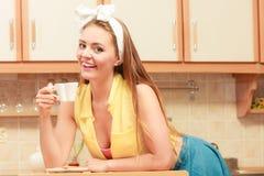 女孩饮用的茶或咖啡的愉快的别针在家 免版税库存图片