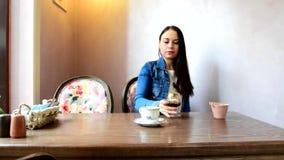 女孩饮用的茶或咖啡,然后喜欢选择一杯酒 股票录像