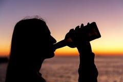 女孩饮用的酒精的剪影从一个瓶的在日落 免版税库存照片