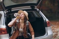 女孩饮用的酒精的画象从瓶的 帽子饮用的威士忌酒的美女 免版税库存图片
