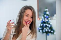 女孩饮用的酒通过圣诞树和想法 坐在圣诞树旁边的美丽的妇女享用杯酒 免版税图库摄影