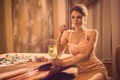 女孩饮用的鸡尾酒在赌博娱乐场 免版税库存照片
