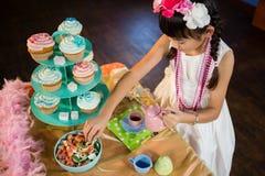 女孩饮用茶和糖果店在桌上在生日聚会期间 免版税库存图片