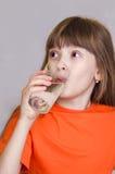 女孩饮用水和微笑 库存图片