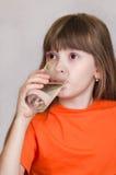 女孩饮用水和微笑 库存照片
