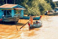 女孩驾驶在Tonle Sap湖的小船的用途桨 库存图片