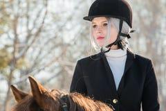 女孩骑师画象骑一匹马的在冬天森林里 免版税库存图片