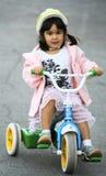 女孩骑马三轮车 库存图片