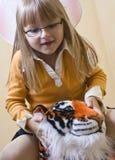 女孩骑马玩具老虎 库存照片