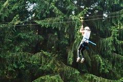 女孩骑马空中览绳在森林冒险钢丝公园 图库摄影