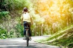 女孩骑马自行车后面看法在庭院里 免版税库存照片