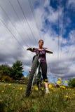 女孩骑马自行车在春天 免版税库存图片