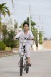 女孩骑马自行车在村庄公园 免版税库存图片