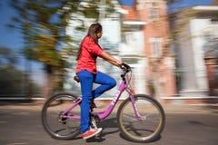 女孩骑马自行车 免版税库存照片