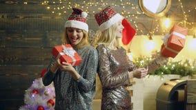 女孩高兴在新年的礼物 Amazed使银色举行新年的礼服和红色帽子的愉快的白肤金发的女孩惊奇 股票视频