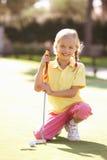 女孩高尔夫球实践的年轻人 库存图片