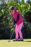 女孩高尔夫球运动员投入 免版税图库摄影