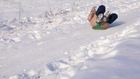 女孩高速滚动在雪橇的高小山下在雪 使用在冬天的愉快的女孩在公园 股票视频