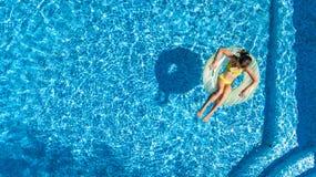 女孩鸟瞰图从上面游泳池的,在可膨胀的圆环多福饼的孩子游泳在水中家庭度假 免版税库存图片
