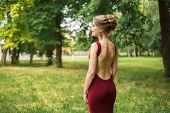 女孩,一件长的腰部配件欢乐晚礼服的妇女与光秃的后面在一个绿色公园站立 库存照片