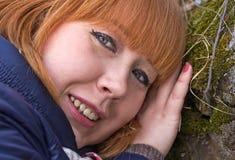 女孩,倾斜反对在猎物的一块生苔石头 库存图片