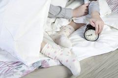 女孩,包裹在一条白色毯子,投入她的手关闭警报 有在闹钟的八个小时 免版税库存图片