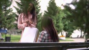 女孩,在购物在包裹后跑由她的朋友决定并且显示她的购买 慢的行动 影视素材