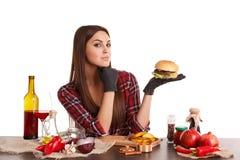 女孩,坐在一张桌上用食物并且拿着一个大开胃汉堡 查出在白色 免版税库存照片